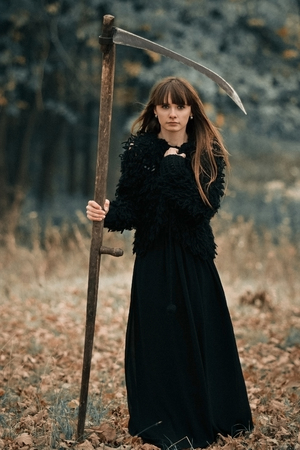 guadaña: Beautiful mysterious mystical girl with long hair in black dress holding a braid in dark autumn forest on the way. Mystical pretty girl in all black clothes with braid stand in dark mystical forest