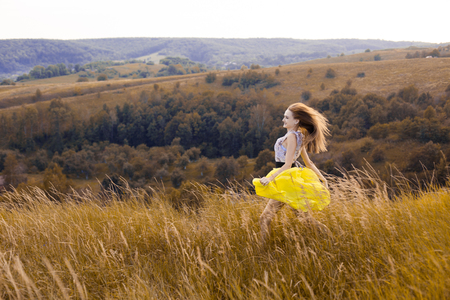 bonne aventure: Happy playful young pretty girl running on the field with green, yellow wheat on the way to good life.Happy adventure in summer, summertime.Cheerful smiling girl in light yellow dress running on field