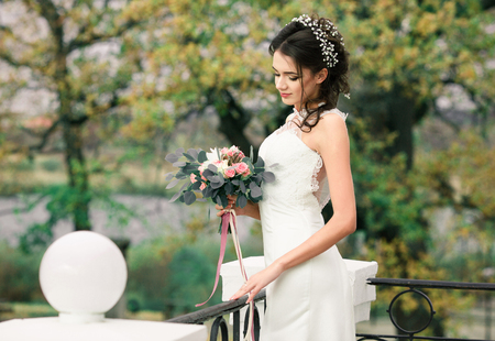 fiancee: Closeup portrait of young gorgeous bride. Pretty beautiful bride with beautiful bouquet of flowers standing in balcony of amazing mansion on spring tress background. Pretty bride with hairstyle. Stock Photo