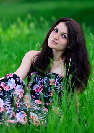 Attractive brunette girl with perfect smile lay on green grass.Pleasant, good, cute, friendly girl with interesting look, eyesight, beautiful dress sit on very bright green grass in summer weather. Stock Photo