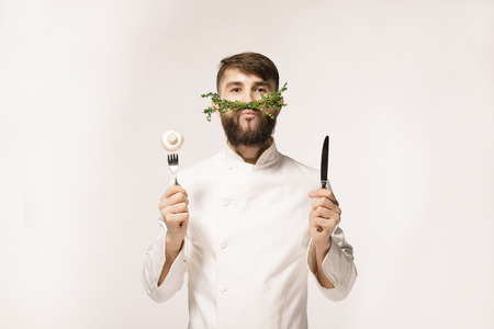Chefs menu logo. Vegan restaurant logo. Symbol of healthy food. CONCEPT OF HEALTHY FOOD. Handsome funny cheff holding spoon and knife and herbs like a mustache. Professional chef.
