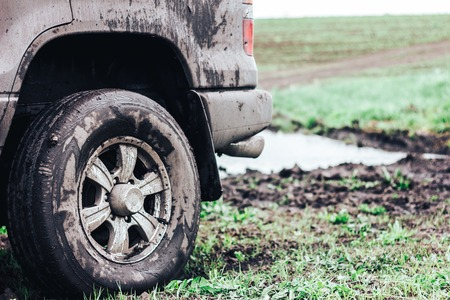 Closeup photo of car wheel dirty next to the river Stock Photo