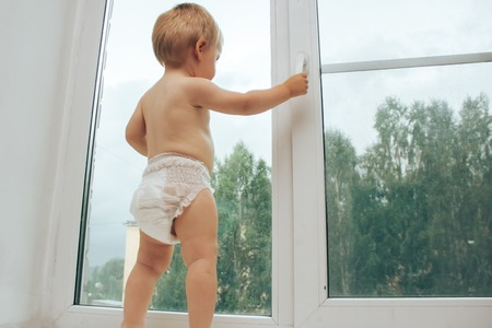 pranks: Girl looking out the window, holding the handle on the window frame Stock Photo