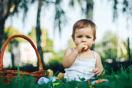 baby eating a biscuit or cookies on grass in a park