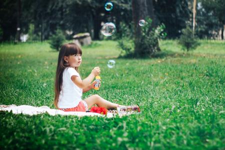 careless: Little beautiful girl blowing soap bubble Stock Photo