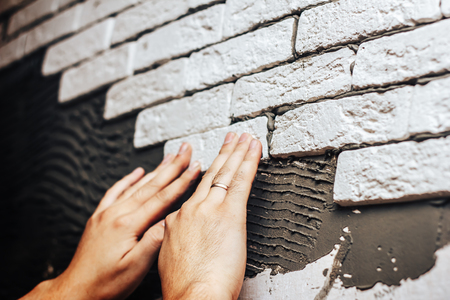 mans hands glue decorative brick on a wall smeared with cement glue