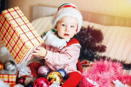 Baby first christmas. Beautiful little baby celebrates Christmas. New Years holidays. Baby with santa hat with gift. Santa baby. Stock Photo