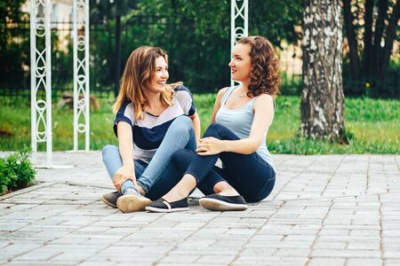 sidewalk talk: Two young beautiful woman best friends in park sitting on sidewalk and talk their tales. Two girls enjoying the weekend in nature