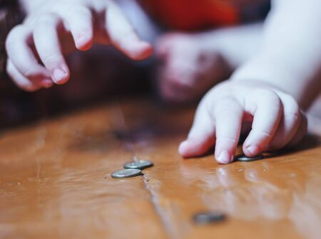 baby plays with coins on floor