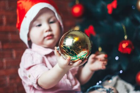 Happy baby in Santa s hat hiding behind a ball against Christmas tree with decorations. Ball in focuse. Baby unfocused.