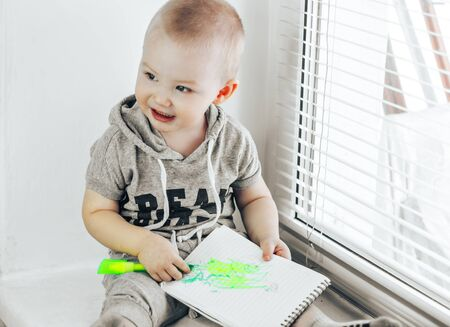 Small child draws on paper. Child holding green marker in hand. Children picture. Preschool drawing activity