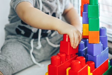 little boy playing, using bright colorful constructor. He put blocks himself.