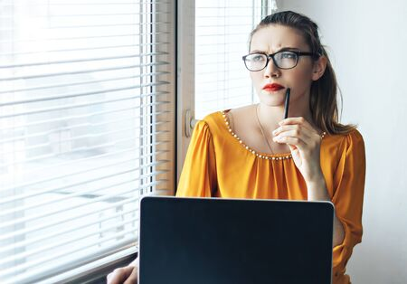 girl near computer thinking in glasses with pen in her hand