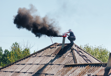 Chimney sweep cleaning a chimney standing balanced on the apex of a house roof lowering equipment down the flue Stockfoto