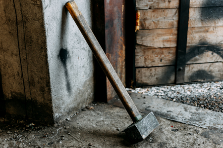 old iron dirty sledgehammer standing indoor in garage