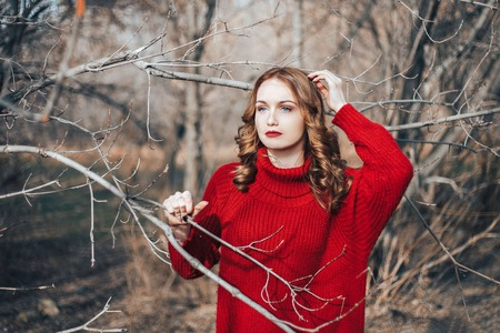 beautiful young girl red hair in red sweater and red dress with makeup and hairdress outdoors in spring forest