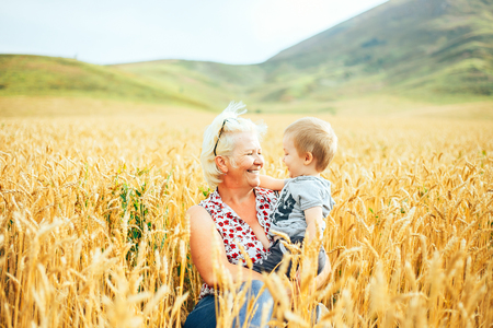 Stylish grandmother admired her little grandchild while standing in the field meadow of ears wheat Imagens - 109365816