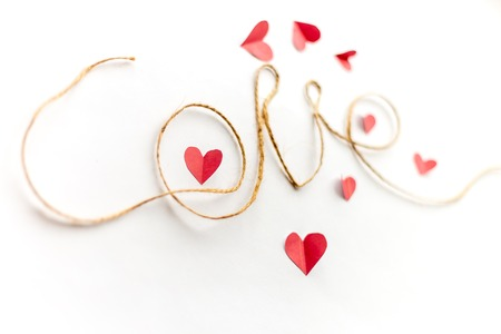 Word love written with rope, on white background, paper hearts around focused on paper heart in letter O