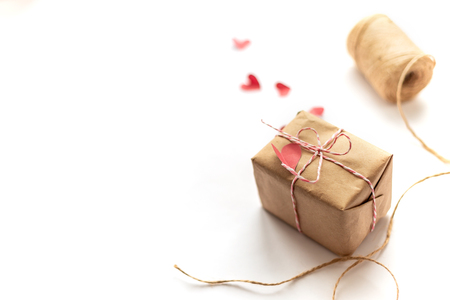 Packages wrapped in kraft paper tied with jute on whte background, focused on gift, selected focus red small paper hearts
