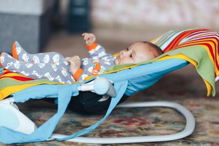 zeer mooie mooie blauwe ogen Baby kind ontspannen op een zonnebank of een ligstoel gekleurde uitsmijter thuis Stockfoto