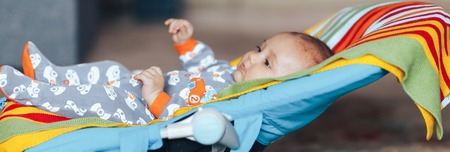 very beautiful nice blue eyed Baby child relaxing on a sunbed or a deck chair colored bouncer at home long banner