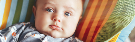 A cute little baby is looking into the camera and is wearing a clother with cars. The baby could be a boy and has blue eyes. parenting or love concept. on colourful plaid long banner