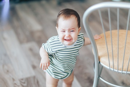 Crying little cutie drk-haired girl, stands crying loudly, standing near chair at home.