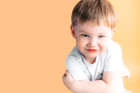 Closeup portrait of an angry boy with his arms folded on orange background.
