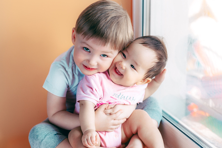 elder brother hugging his baby sister playing and smiling together. family concept love protect.