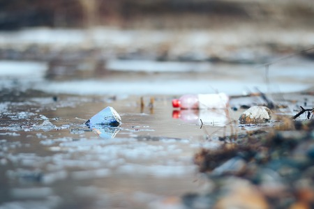 Abandoned empty pink plastic bottle and blue can garbage at the river bank conservancy pollution. Banco de Imagens