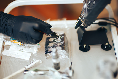woman prepare instruments for permanent makeup to work pigment drop to palette.