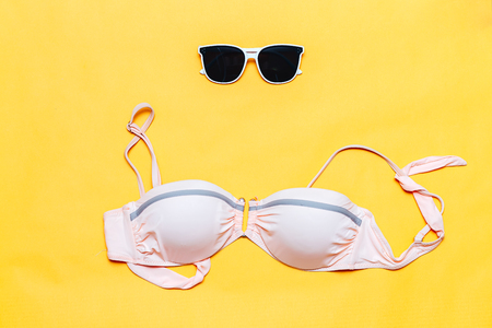 Summer accessories concept on yellow background, flatlay, copyspace, vintage camera, white sunglasses and swimsuit, towel. Flat lay photo, travel concept. Free space for text, mock-up Stockfoto