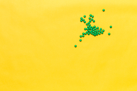 small green round pills tablets on yellow background. copyspase, space for text. Imagens