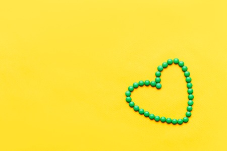 green round pills tablets heart shape on yuellow background.
