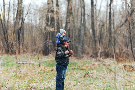 Happy weekend concept. happy grandfather and grandson are walking in forest. Spring. Grandpa rolls on the shoulders of a little boy.