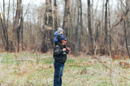 Happy Weekend-Konzept. glücklicher Großvater und Enkel gehen im Wald spazieren. Feder. Opa rollt auf den Schultern eines kleinen Jungen.