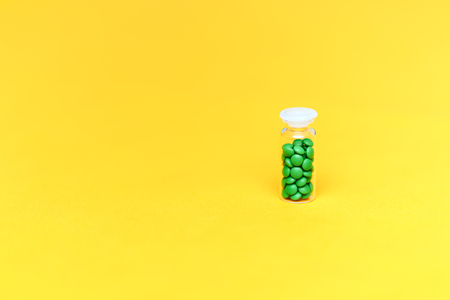 Medical green pills in a glass bottle on yellow background copyspace, health. Imagens