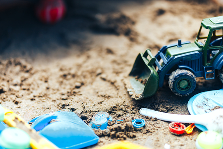 Summer Childrens Toys on the sand, sand box, green tractor.