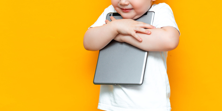 happy cute boy hugging his lovely tablet computer pc, Z generation, children who was born with technology.