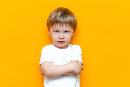 Portrait of angry little boy with arms folded isolated on yellow background. Sad and unhappy child. Upset toddler boy.