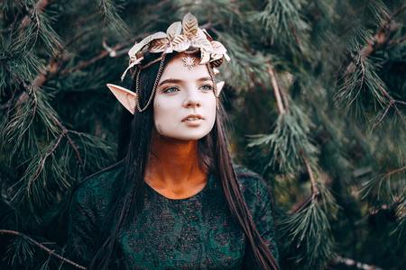 schöne Elfenfrau fabelhaft, Märchenwald, famtasy junge Frau mit langen Ohren, lange dunkle Haare goldene Kranzkrone auf dem Kopf