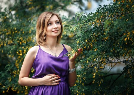 beautiful Pregnant european woman in purple violet dress, standing near bushes of acacia with yellow small flowers, block colours.