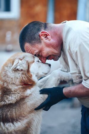 mature man in gloves hugging red husky dog forehead to forehead, eyes o eyes, care friendship concept.