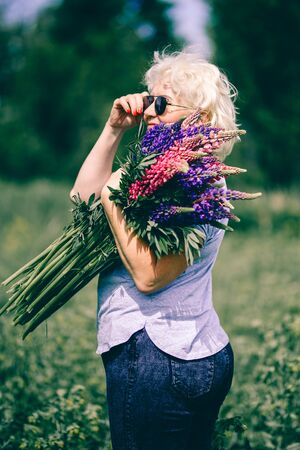 Blonde mature stout woman holding a lupine bouquet on nature background. The concept of beauty and Body Positive. Sunset light.