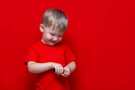 little child boy pours pills from the can into the hand,healthy concept. It is dangerous tablets in babies hands. red background