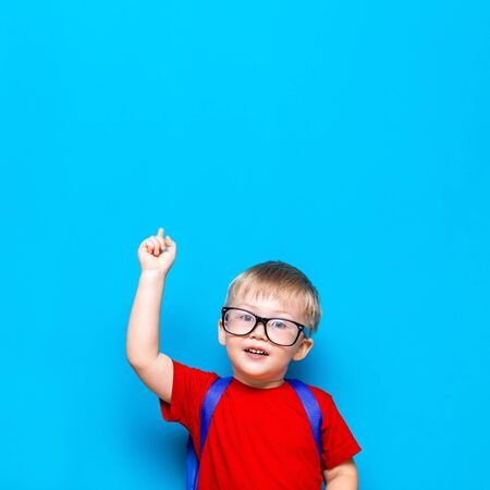 Back to school First grade junior lifestyle. Small boy in red t-shirt. Close up studio photo portrait of smiling boy in glasses with schoolbag and book show somethind with his finger up, over his head.