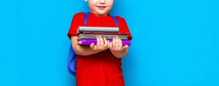 Smiling happy cute clever boy with backpack. Child with a pile of books in his hands. blue background. Ready for school. Back to school.