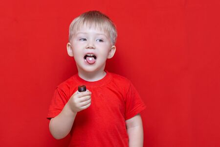 small three years old boy wants to eat pill, tablet on his tongue, can bottle in hand. red background.