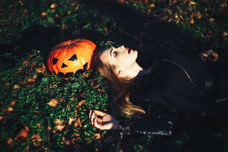 beautiful young blond woman with extravagant make-up in a black leather jacket with wide open eyes and an open mouth with a pumpkin in hands.