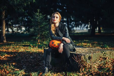 Beautiful modern witch holding halloween pumpkin in the forest. october. happy holidays. Stock Photo